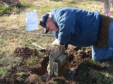 Garry Walls reaches to clean a sunken stone
